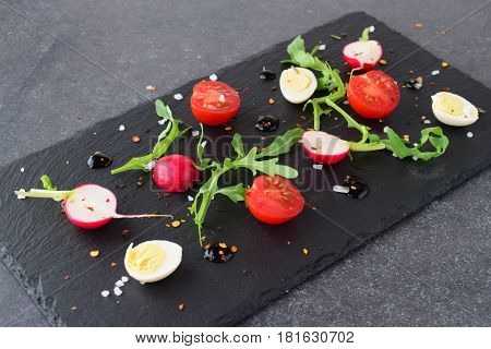 Fresh radish, cherry tomato, quail egg, ruccola with balsamic glaze on a black stone plate. Mediterranean lifestyle. Healthy food
