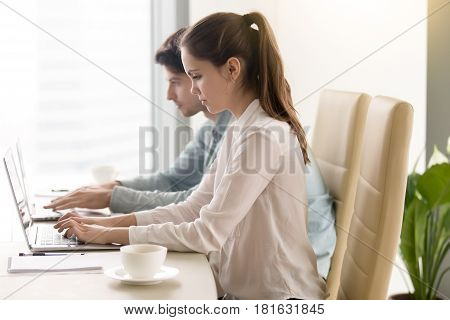 Side view of young busy woman and man sitting side-by-side at the office table looking at their laptops, colleagues focused on working, teamwork or coworking