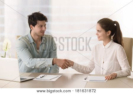 Smiling businessman handshaking with young businesswoman before office meeting or discussion, starting teamwork on project, interesting acquaintance, beginning of the course