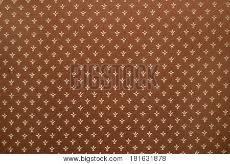 Brown textile background with royal lily or fleur-de-lis pattern on cloth texture