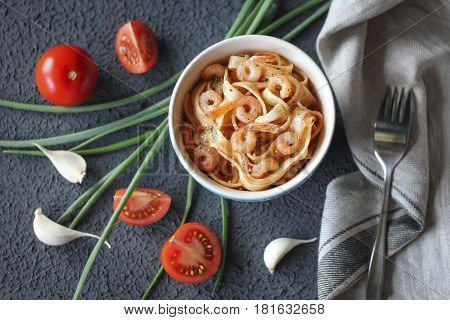 Tagliatelle pasta with shrimps and tomato sauce on dark background. Italian cuisine. Top view
