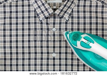 Steam iron in green with aluminum soleplate, water in tank, ironing blurred checked clothes black white shirt