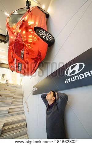 MOSCOW - APR 16 2016: Hyundai Solaris on wall and man looks up (with model release) in Hyundai Motorstudio. Hyundai produces not only cars, but also its own collection of furniture and household items