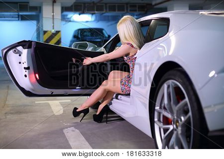 MOSCOW - MAY 20, 2016: Beautiful woman (with MR) sits in white Lamborghini Huracan LP 610-4. Lamborghini Huracan is world first production car, using inertial navigation system