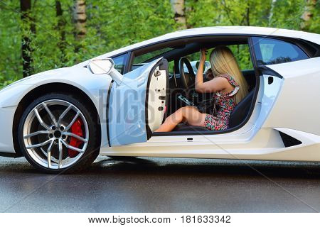 MOSCOW - MAY 20, 2016: Woman (with MR) sits in white Lamborghini Huracan LP 610-4. Lamborghini Huracan is world first production car, using inertial navigation system