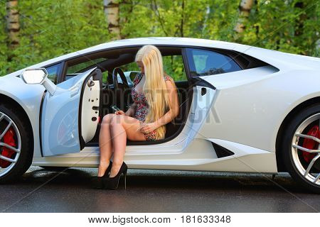 MOSCOW - MAY 20, 2016: Pretty woman (with MR) sits in white Lamborghini Huracan LP 610-4. Lamborghini Huracan is world first production car, using inertial navigation system