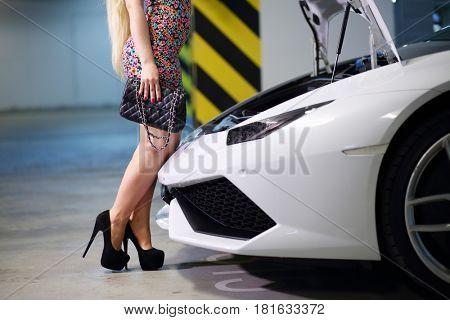 MOSCOW - MAY 20, 2016: Woman (with MR) opens hood of Lamborghini Huracan LP 610-4. Lamborghini Huracan is world first production car, using inertial navigation system