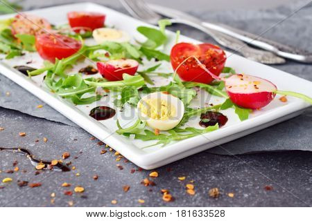 Fresh radish, cherry tomato, quail egg, ruccola with balsamic glaze on a white plate. Mediterranean lifestyle. Healthy food. Selective focus