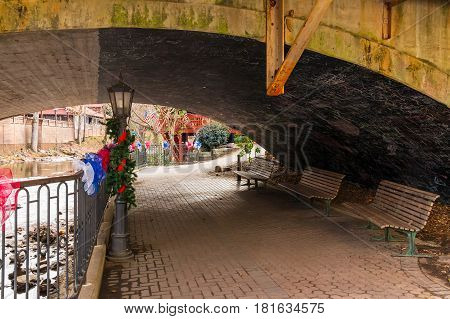 The passage with benches on the embankment on the Chattahoochee river under bridge Helen USA