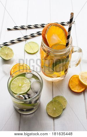 Water with ice and lime in a glass jar and a white wooden background