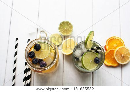 Flat lay. Refreshing lemonade in jar and glass with lime and orange on a white wooden table