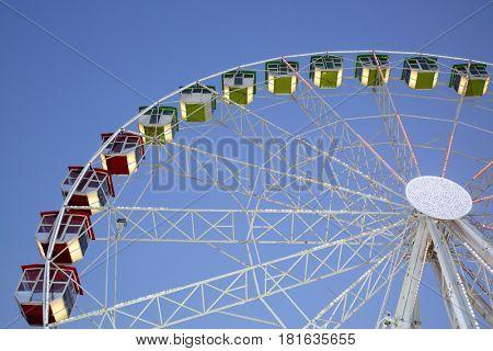 Ferris wheel illuminated in flashing lights on blue sky background