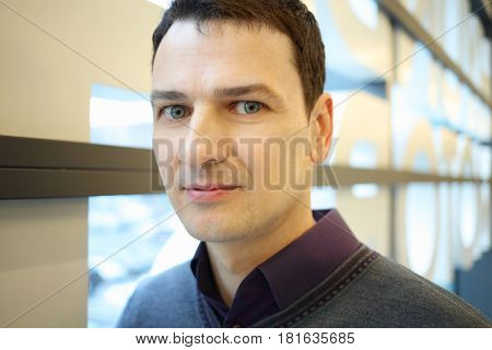 Happy handsome brunet man poses in shopping center, close up