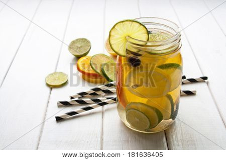 jar refreshing drink with orange and lime on a white wooden table