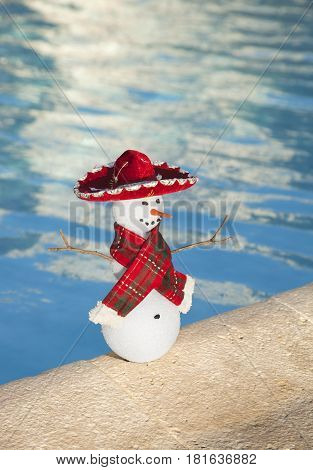 A miniature snowman with a red scarf and sombrero by the edge of a pool in Cancun Mexico