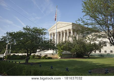 United States Supreme Court building with flag and trees in afternoon sun