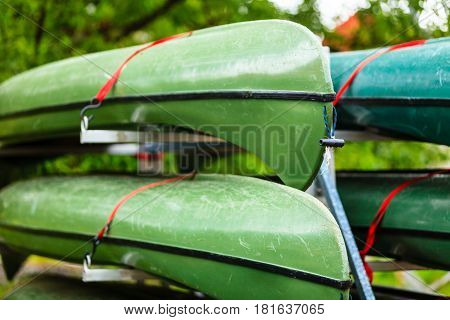 Active lifestyle sport concept. Car with many stacked canoes ready to transportation closeup