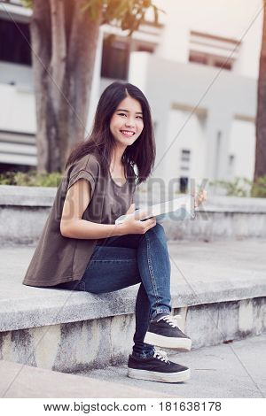 University college teen girl reading and education. Beautiful Asian woman study read the book in the morning.