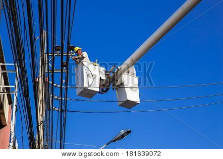 engineer electricians repairing electricity power line at high place of electric pole on crane against blue sky.
