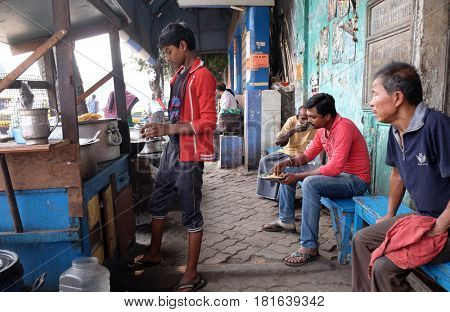KOLKATA, INDIA - FEBRUARY 08: Street trader sells fast food for hungry people on the busy street in Kolkata, India on February 08, 2016.
