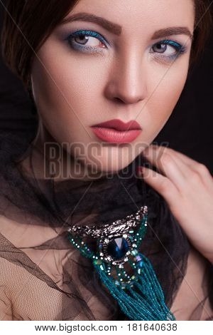 Portrait of beautiful brunette fashion model with black veil and blue jewelry and makeup and red lips in black bakground.