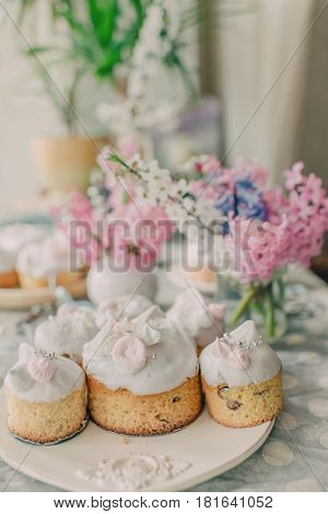 On a beautiful dish decorated with pink frosting Easter cakes and hyacinths