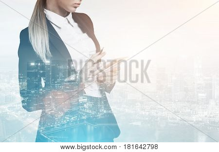 Portrait of an unrecognizable businesswoman writing in her notebook while standing against a blue city panorama. Toned image double exposure mock up
