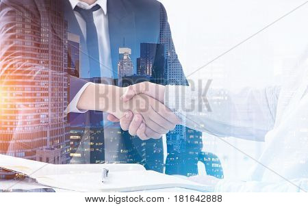 Close up of two business partners shaking hands at a table. There is a morning city panorama in the foreground. Toned image double exposure.