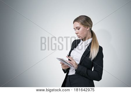 Portrait of a serious blond woman wearing a black and white business suit writing in her small notebook. Gray background. Mock up