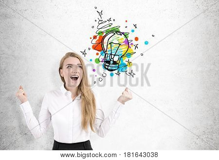 Portrait of a happy blond businesswoman shouting with joy while standing near a concrete wall with a little colorful light bulb sketch