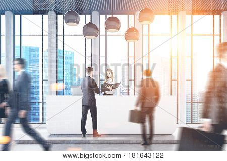 Businesspeople are passing by a reception counter in an office with a skyscraper seen through a panoramic window. 3d rendering toned image double exposure
