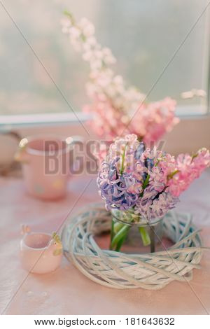 On the table there is a bouquet of a pink hyacinth in a glass vase with a wreath and a pink cup of a chicken