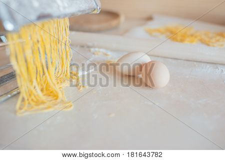 On a wooden table in flour home-made noodles and eggs. Wooden rolling pin