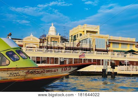 Bangkok, Thailand - January 9, 2016: Yodpiman Riverwalk is largest lifestyle shopping mall on the Chao Phraya River in the heart of the tourist centre of Bangkok. Express boat floats in the foreground