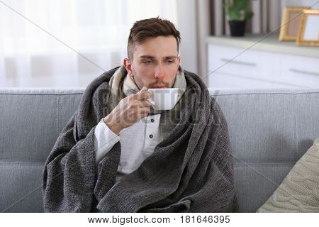 Ill man in blanket drinking hot tea on couch at home