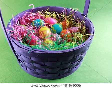 Colorful plastic eggs in artificial grass in a wooden woven basket ready for the Easter season.