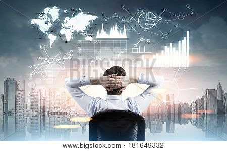 Rear view of a businessman sitting in a city with his hands behind the head and looking at graphs in the air. Toned image.