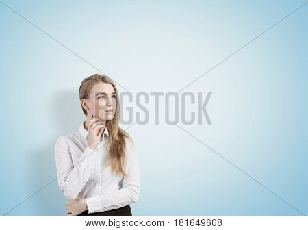 Portrait of a pensive blond businesswoman wearing a white blouse and a black skirt and looking sideways. Blue background. Mock up