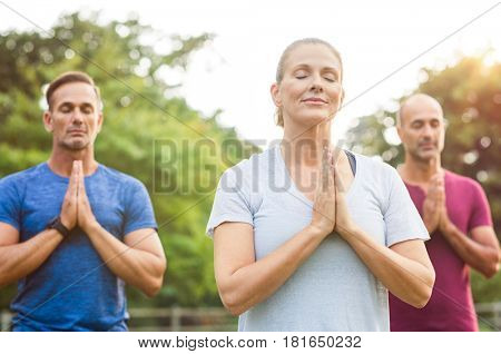 Three people at park meditating with joined hands and closed eyes. Senior woman and mature men doing breath exercise outdoor. Group of people doing yoga with joined hands and relaxing together.
