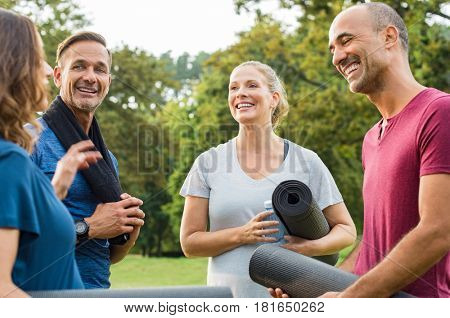 Happy multiethnic group of mature people holding yoga mat and towel in conversation after exercising at park. Senior men and smiling women talking to each other after an exercising class outdoor.