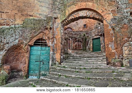 Pitigliano, Tuscany, Italy: ancient staircase cellar doors and medieval city door