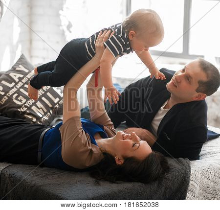 Young parents with small baby lie on bed and toss it up. They laugh fun.