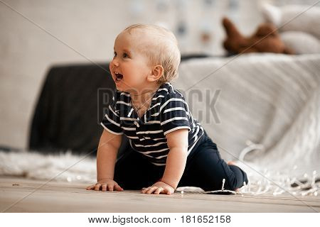 Small baby crawling on floor and laughs merrily. He is very pleased.