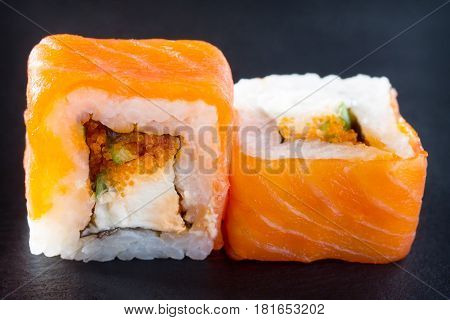 Roll Jamaica Isolate On A Black Slate Board - Tobiko Orange Salmon, Salmon, Soft Cheese, Cucumber, N