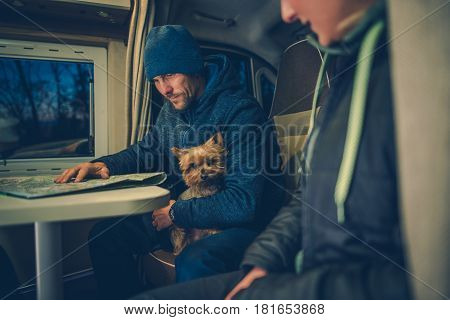 Young Caucasian Couples with Australian Silky Terrier Dog Traveling in Their RV Motorhome. Men Studying Map on the Camper Table.