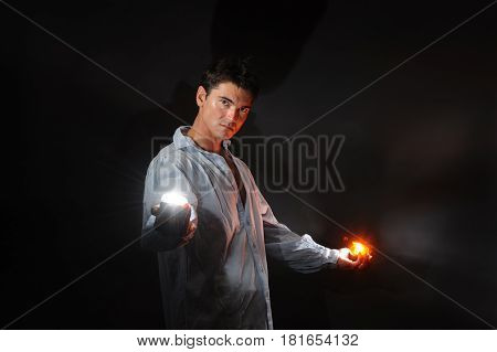 The cute guy is holding a couple of lights.