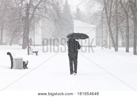 Bad weather in a city: a heavy snowfall and blizzard in winter. Male pedestrian hiding from the snow under umbrella