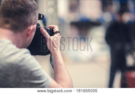Studio Photo Session. Caucasian Photographer Taking Picture of His Model Using Professional Photography Gear.