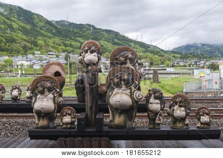 Kameoka Japan - March 2016: Statues of Japanese raccoon dog or tanuki at Torokko Kameoka Station terminal station for Sagano Scenic Railway or romantic train from Arashiyama