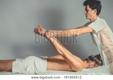 Massage stretching therapy. A young professional male masseur makes Thai massage. Patient is lying down on a bed and is covered with white towel. Treatment, rest, relaxation, spa. Studio shot